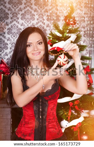 Christmas woman with New Year Tree and xmas gift. Winter concept/ Portrait of Happy Christmas girl at home. Happy New Year. Luxury house at New Year. - stock photo