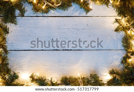 Christmas wood background with luminous garland and pine branches