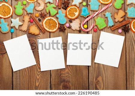 Christmas wooden background with photo frames, candies, spices and gingerbread cookies - stock photo