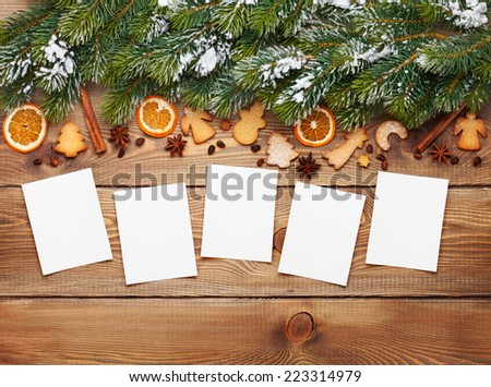 Christmas wooden background with photo frames, snow fir tree, spices and gingerbread cookies - stock photo