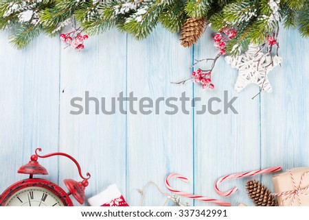 Christmas wooden background with snow fir tree, alarm clock and gift box. Top view with copy space - stock photo