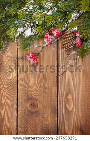 Christmas wooden background with snow fir tree and decor with copy space - stock photo