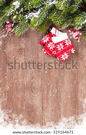 Christmas wooden background with snow fir tree and mittens - stock photo
