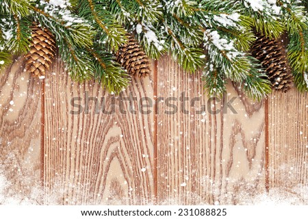 Christmas wooden background with snow fir tree and pinecones - stock photo