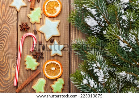 Christmas wooden background with snow fir tree, spices, gingerbread cookies - stock photo