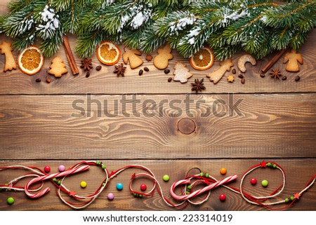 Christmas wooden background with snow fir tree, spices, gingerbread cookies and copy space - stock photo