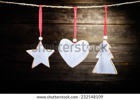 christmas wooden decorations - star, heat and christmas tree hanging on rope in front of wooden background - stock photo