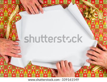 Christmas wrapped present being ripped open by four hands - stock photo