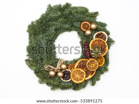 Christmas wreath decorated with oranges isolated on white background