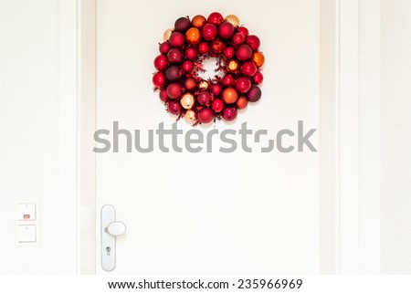 Christmas wreath decorated with red balls on white entrance door to a flat - stock photo