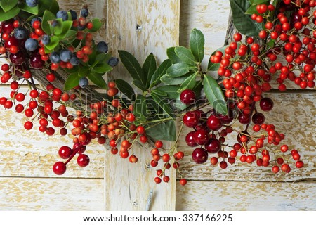 Christmas wreath detail of evergreen and berries on wooden background. Natural Nandian network, green branch and rustic wood crown - stock photo
