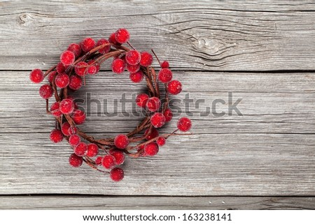 Christmas wreath from red berries on wooden background - stock photo