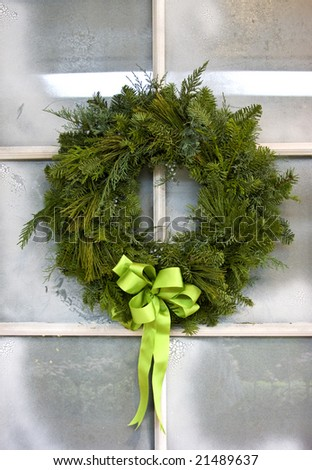 Christmas wreath hanging from a frosted glass pane door. - stock photo