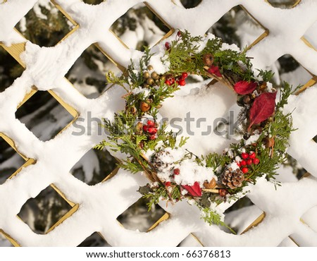 Christmas wreath hanging on a snow covered lattice wall with copy space. - stock photo
