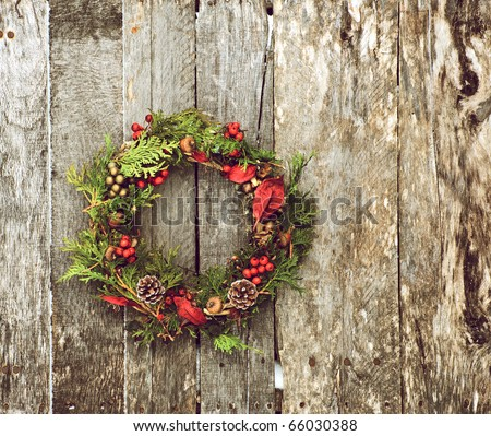 Christmas wreath (home made) with natural decorations hanging on a rustic wooden wall with copy space.