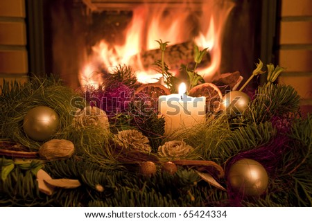 Christmas wreath in front of the fireplace. - stock photo