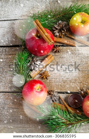 Christmas wreath made of fir branches, cones, red apples and cinnamon. Snowing - stock photo