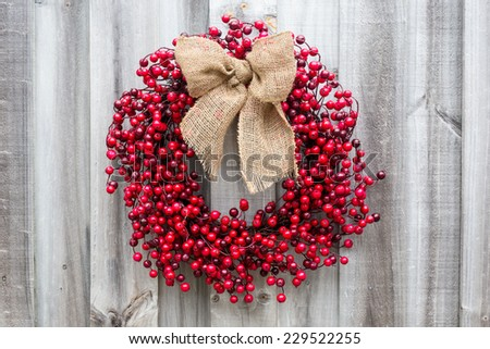Christmas wreath made of holly berries tied with a burlap bow hangs on old weathered wood. Vintage filters applied.  - stock photo
