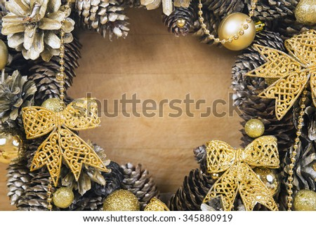 Christmas wreath of cones and gold balls close-up on wooden background. - stock photo