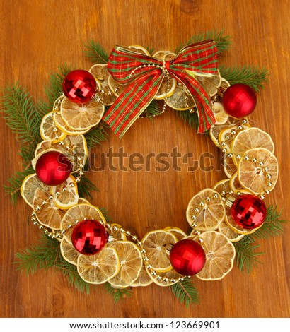 christmas wreath of dried lemons with fir tree and balls, on wooden background - stock photo