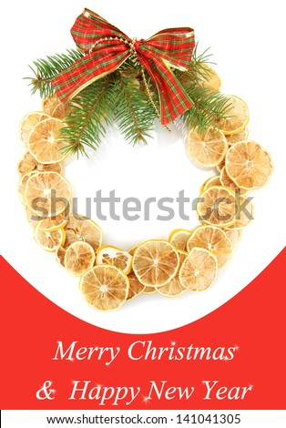 Christmas wreath of dried lemons with fir tree and bow - stock photo