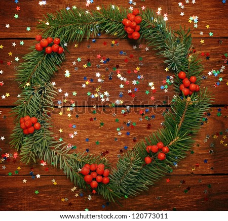 Christmas wreath of fir branches on the wooden background