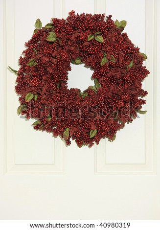 Christmas wreath of red berries hanging on a front door. - stock photo