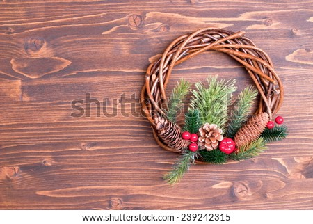 Christmas wreath of twigs with pine needles and cones on a brown board - stock photo
