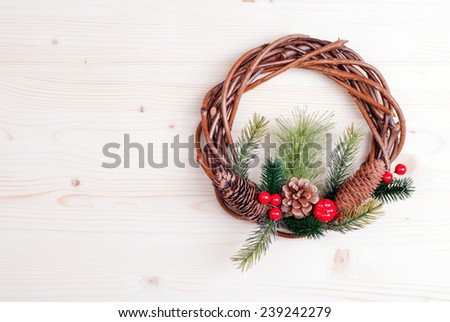 Christmas wreath of twigs with pine needles and cones on light board - stock photo