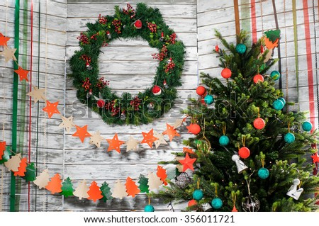 Christmas wreath on a white wooden wall with garlands