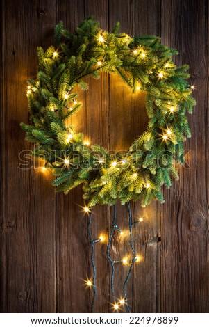 Christmas wreath on a wooden door - stock photo