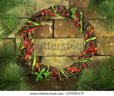Christmas wreath on chimney place decorated with conifer branches - stock photo