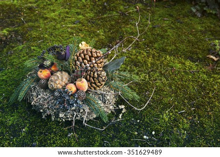 christmas wreath on moss with pine cones and branches - stock photo
