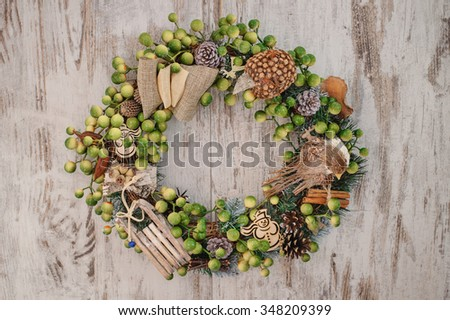 Christmas wreath on the wooden background with wooden toys - stock photo