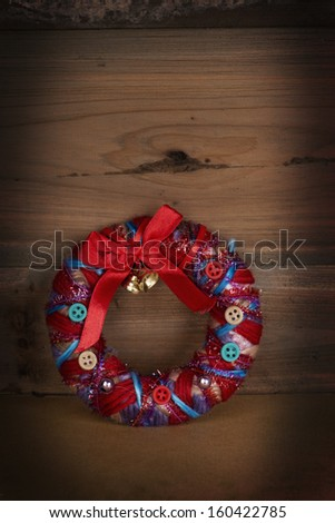 Christmas Wreath on wooden background with vignette - stock photo