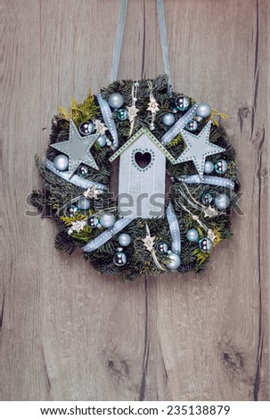 Christmas wreath on wooden door with blue decorations, space for your text  - stock photo