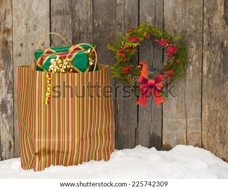 Christmas wreath with a pretty male cardinal peeking out hanging on a rustic wooden wall beside a colorful bag filled with Christmas gifts.  - stock photo