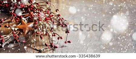 Christmas wreath with berries and rusty stars on wooden background. Falling snow effect. Vintage Style. Long narrow format. Copy space. Toned image - stock photo