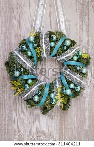 Christmas wreath with blue and silver decorations on wooden door, space for your text - stock photo