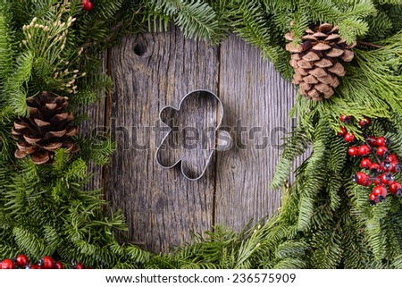 Christmas Wreath with Gingerman Cookie in the Middle of Wood Background - stock photo