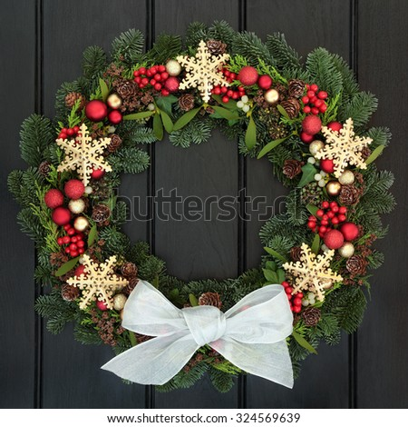 Christmas wreath with gold snowflake and red bauble decorations, holly, mistletoe and winter greenery over dark oak front door background. - stock photo