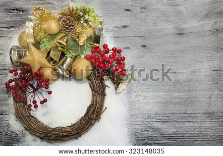Christmas wreath with golden balls, bells, snow  and red berries  on the wooden background - stock photo