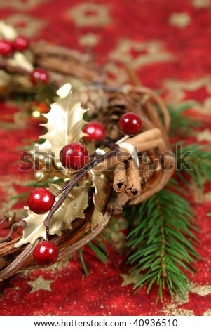 Christmas wreath with golden holly leaves, cones, red berries, cinnamon and twig spruce on red textile with gold stars. Shallow DOF - stock photo