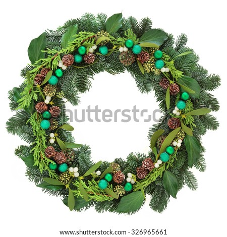 Christmas wreath with green bauble decorations, mistletoe, ivy, pine cones and blue spruce fir over white background. - stock photo