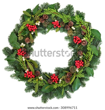 Christmas wreath with holly, ivy, mistletoe and winter greenery over white background. - stock photo