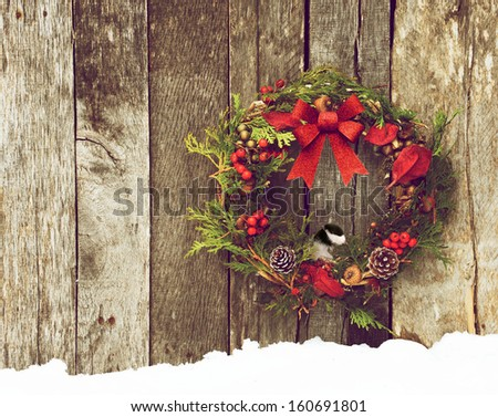 Christmas wreath with natural decorations, a big red bow,  and a cute little chickadee peeking out hanging on a rustic wooden wall with copy space.  - stock photo