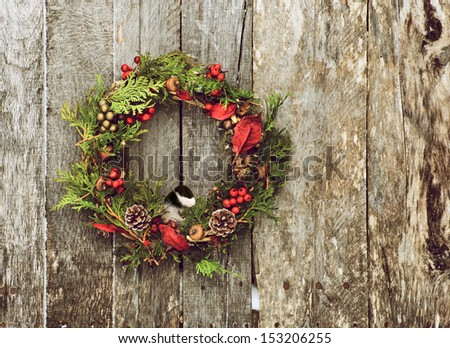 Christmas wreath with natural decorations and a cute little chickadee peeking out hanging on a rustic wooden wall with copy space.