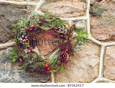 Christmas wreath with natural decorations hanging on a rustic stone wall with copy space. - stock photo