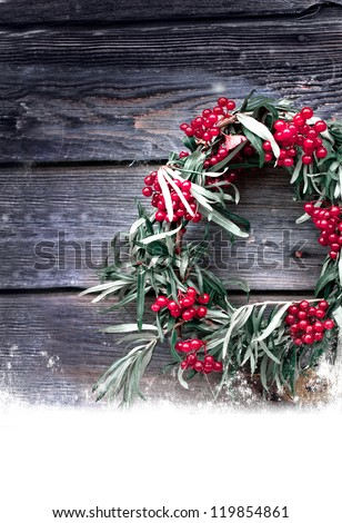 Christmas wreath with natural decorations hanging on a rustic wooden wall with copy space with a snow/holidays background - stock photo