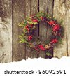 Christmas wreath with natural decorations hanging on a rustic wooden wall with snow and copy space. - stock photo